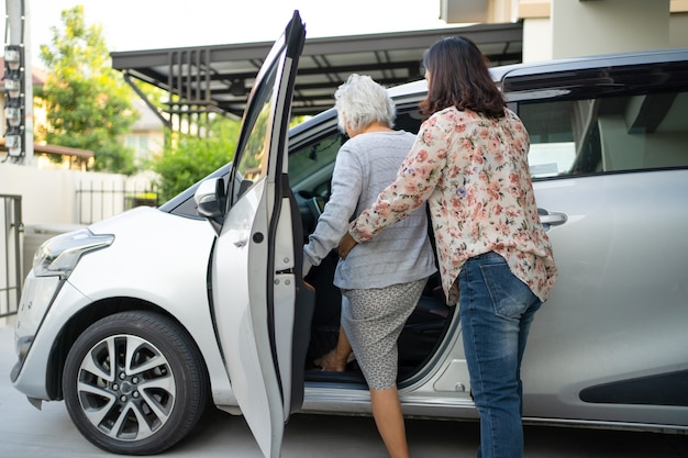 Ajudar e apoiar o paciente asiático de mulher idosa sênior ou idosa se preparar para chegar ao carro dela.