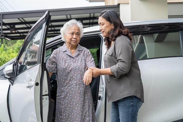 Ajudar e apoiar uma paciente asiática idosa sentada em uma cadeira de rodas se preparando para chegar ao carro