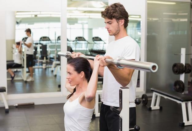 Ajude a mulher a levantar a barra com seu instrutor