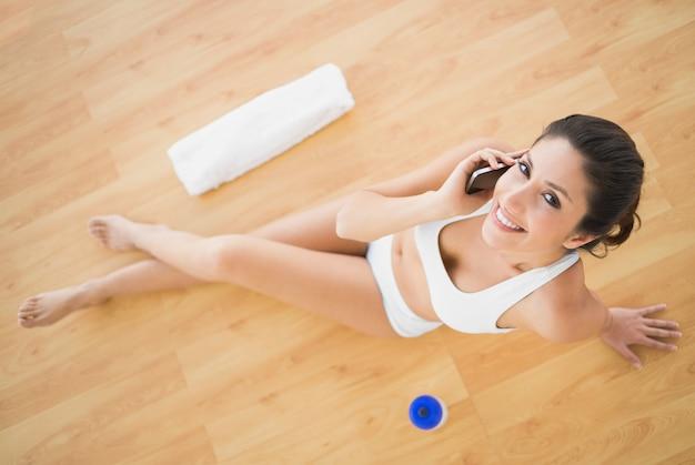 Ajude a mulher feliz a fazer uma chamada durante o treino olhando a câmera