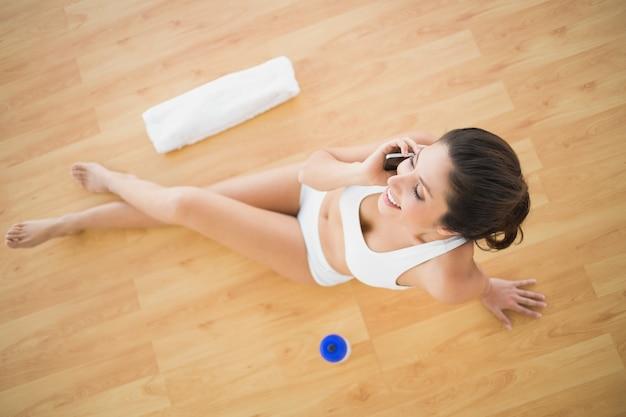 Ajude a mulher feliz a fazer uma chamada durante o treino