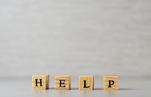 Ajude a palavra feita de letras e cubos de madeira