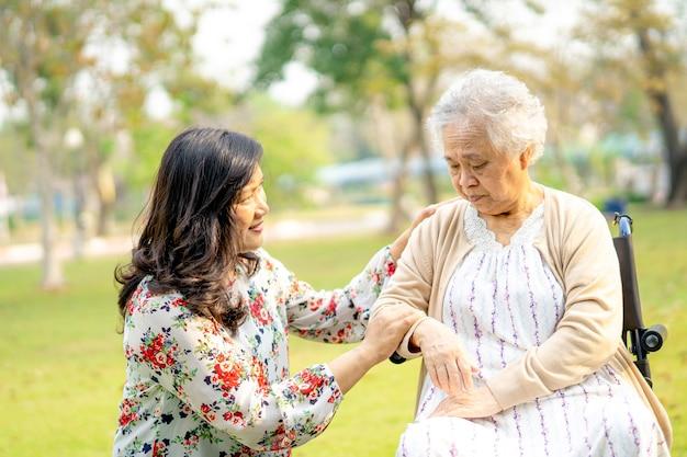 Ajude e importe-se o paciente sênior asiático da mulher no parque.