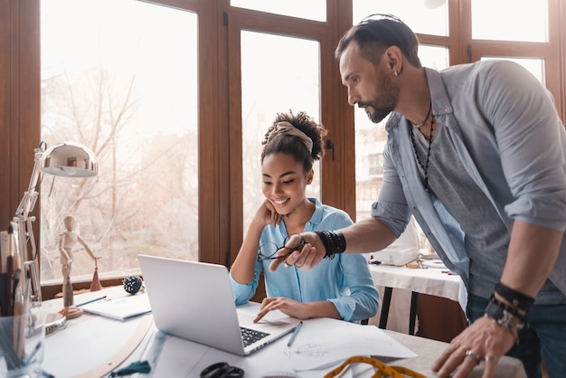 Ajude o colega com o projeto. homem e mulher no estúdio de design. homem dá algumas dicas para a designer africana.