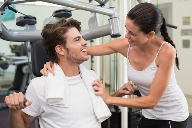 Ajude o homem a usar máquina de pesos com o treinador encorajando-o