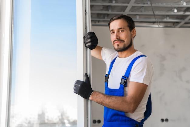 Ajustador em luvas instala a janela do apartamento