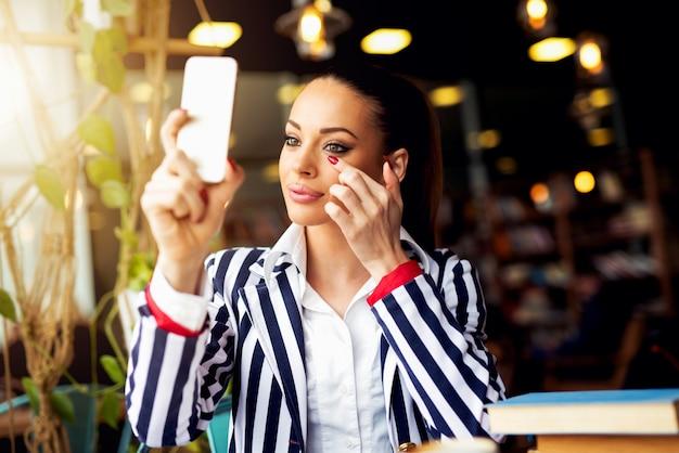 Ajustando a maquiagem no café bar, olhando no espelho.