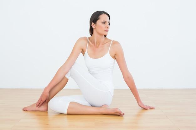 Ajustar a mulher fazendo a torção da medula mediana no estúdio de ginástica