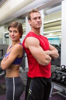 Ajustar o casal atraente sorrindo para a câmera com os braços cruzados