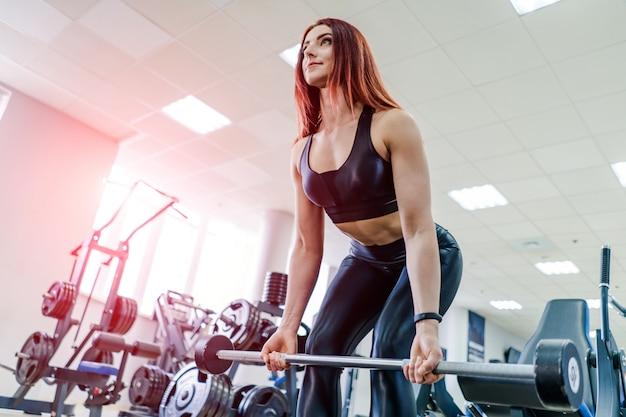 Ajuste a barra de levantamento da jovem mulher que olha focalizada, malhando em uma academia. mulher jovem e bonita exercícios com barra.