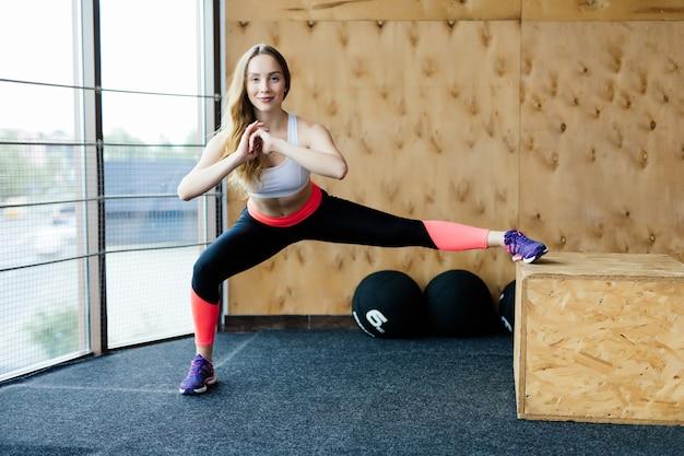 Ajuste a caixa de jovem pulando em um ginásio de estilo crossfit. atleta feminina está realizando saltos de caixa no ginásio.