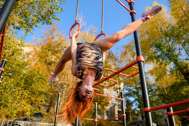 Ajuste a fêmea jovem fazendo exercícios de pull ups na barra transversal ao ar livre esporte e conceito de estilo de vida saudável.