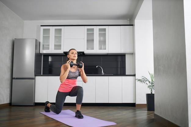 Ajuste a garota vestindo roupas esportivas, treinamento em casa pela manhã, usando halteres.