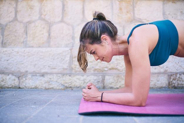 Ajuste a jovem mulher fazendo pranchas. feche a foto do retrato. atleta feminina, exercitando-se fora da cidade, em uma esteira. usando sutiã azul.