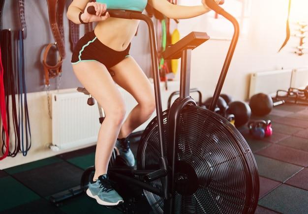 Ajuste a jovem treina na bicicleta do ar no ginásio. cardio antes do treinamento de força principal, treinamento funcional