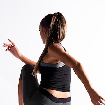 Ajuste a menina no terno de ginástica exercício dentro de casa