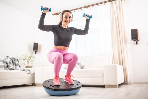 Ajuste a mulher bonita em uma roupa de treinamento e agachamentos de fones de ouvido em casa em uma bola de equilíbrio segurando halteres para cima.