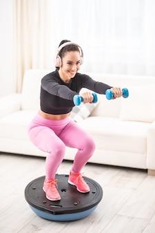 Ajuste a mulher bonita em uma roupa de treinamento e agachamentos de fones de ouvido em casa em uma bola de equilíbrio segurando halteres.