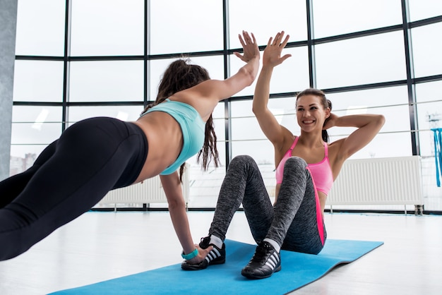 Ajuste a mulher jovem sorridente dando mais cinco para seu personal trainer enquanto fazia exercícios abdominais em uma esteira no ginásio
