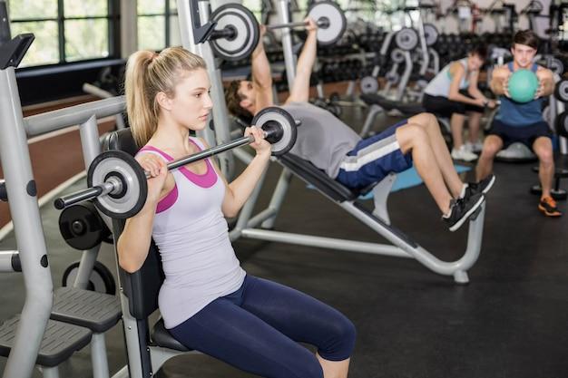 Ajuste a mulher levantando a barra no ginásio crossfit