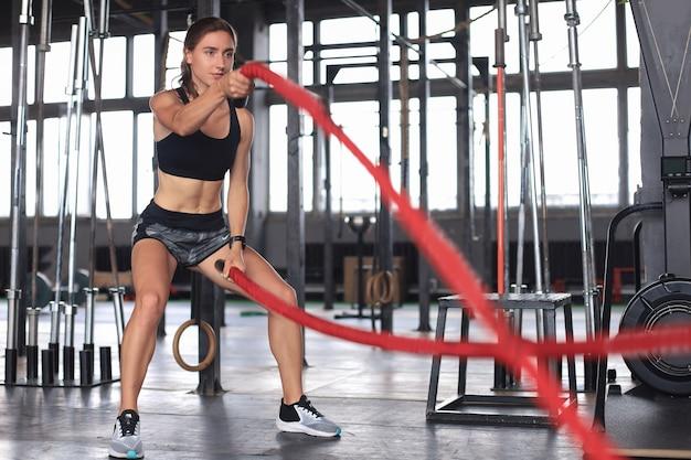Ajuste a mulher usando cordas de batalha durante o treinamento de força no ginásio.