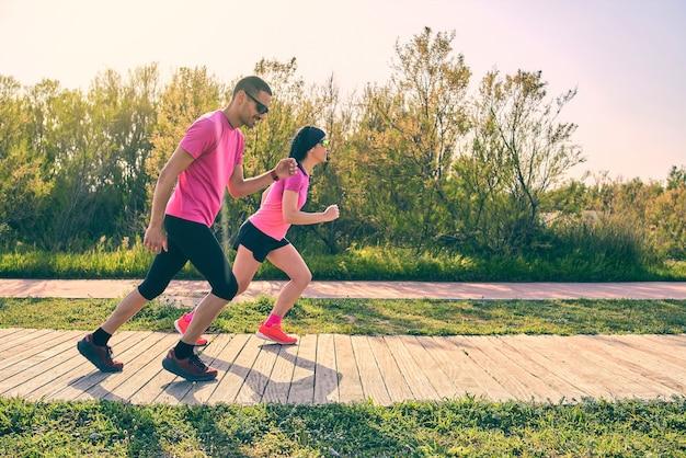 Ajuste a técnica de treinamento de casal para evitar lesões. vestindo camisas cor de rosa. ambos estão vestindo roupas esportivas.