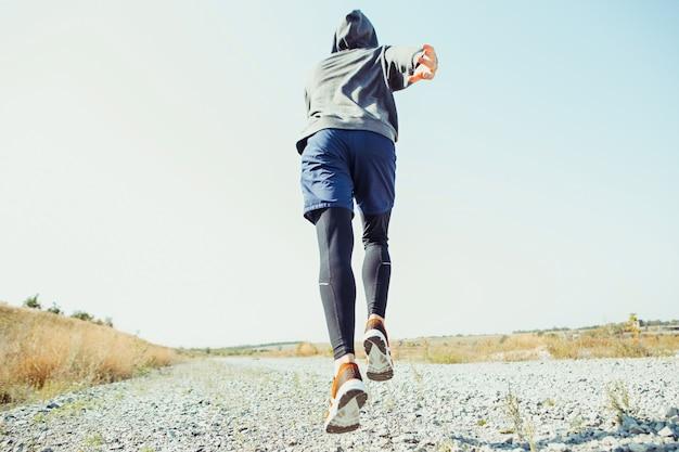 Ajuste a trilha de treinamento muscular do atleta masculino correndo para a maratona