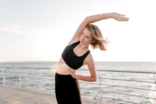 Ajuste adolescente fazendo exercícios de esporte pela manhã na praia
