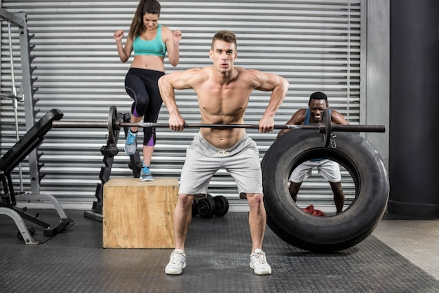 Ajuste as pessoas exercitando juntos no ginásio crossfit