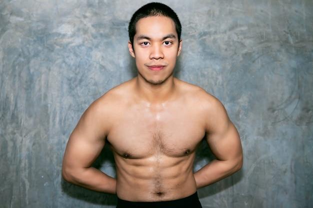 Ajuste asiático atlético do homem e sorriso saudável no gym após o exercício.