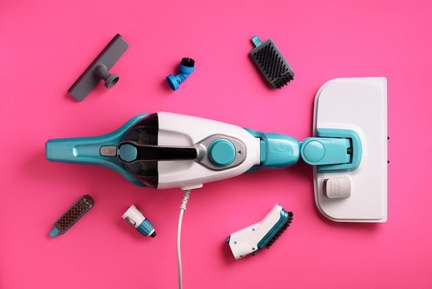 Ajuste com limpadores de vapor profissionais modernos no fundo cor-de-rosa. conceito de serviço de limpeza