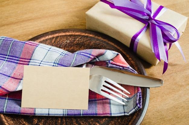 Ajuste da mesa de jantar com tag e presente vazios.