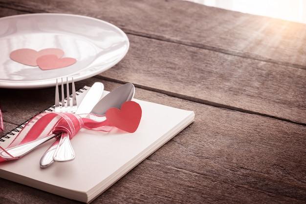 Ajuste da tabela do dia de valentim com placa, faca, forquilha, fita vermelha, caderno.