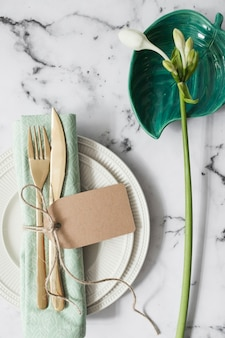 Ajuste de lugar com placas brancas; guardanapo dobrado e talheres com flores brancas