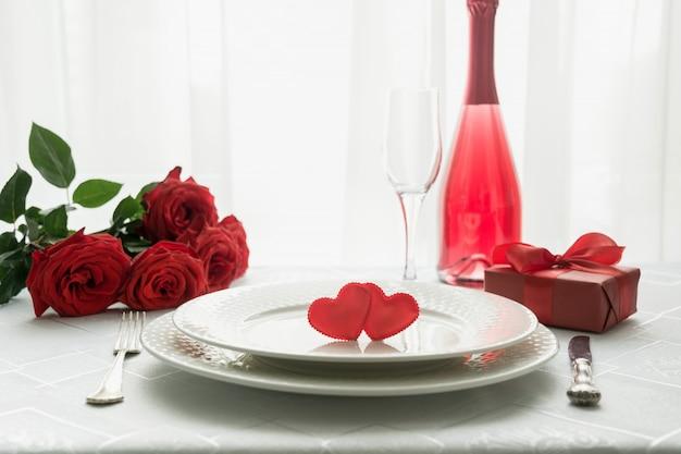 Ajuste de lugar da tabela do dia de valentim com rosas vermelhas e champanhe. convite para uma data.