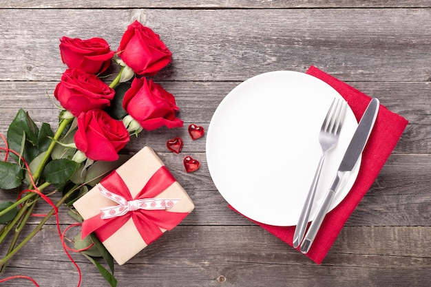 Ajuste de lugar de dia dos namorados com buquê de rosas, corações vermelhos e talheres na mesa de madeira cinza. vista do topo. copiar espaço - imagem