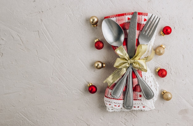 Ajuste de lugar de mesa de natal com talheres em guardanapo e bugiganga de decorações festivas.