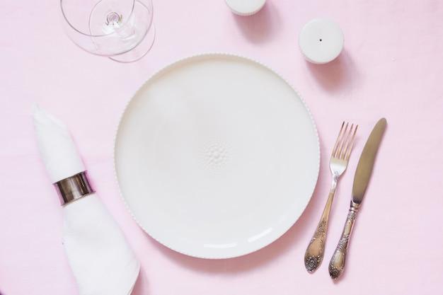 Ajuste de lugar de mesa na toalha de mesa de linho rosa. vista do topo.