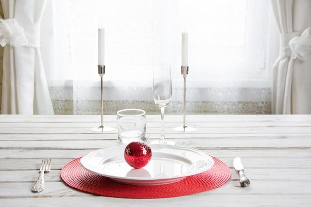 Ajuste de lugar do natal com dishware branco e decorações vermelhas no branco.