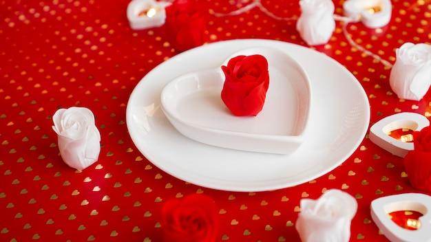 Ajuste de lugar em vermelho e branco - para o dia dos namorados ou outro evento. prato branco em forma de coração com decoração de rosas em fundo vermelho
