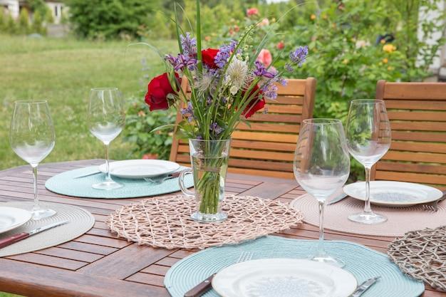 Ajuste de mesa de banquete fino com buquê no jardim. conceito de festa