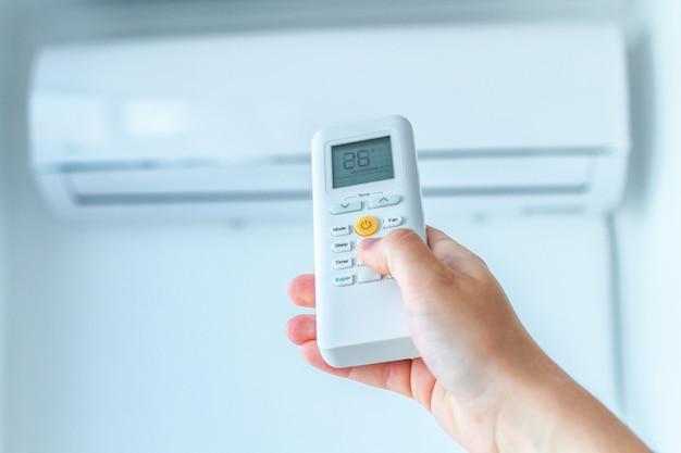 Ajuste de temperatura do ar condicionado com controle remoto no quarto em casa.