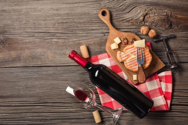 Ajuste do jantar do feriado com vinho tinto e queijo de desnatação na madeira rústica.