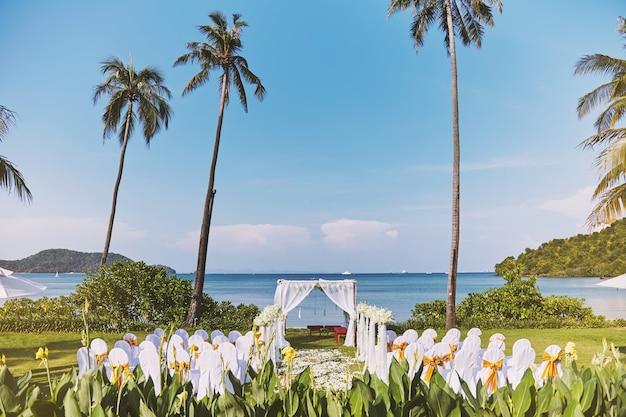 Ajuste do local do casamento de praia com palmeira de coco e vista panorâmica do mar