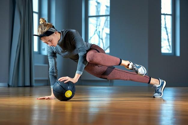 Ajuste e mulher muscular fazendo treino intenso do núcleo com kettlebell no ginásio. mulher exercitando na academia crossfit.