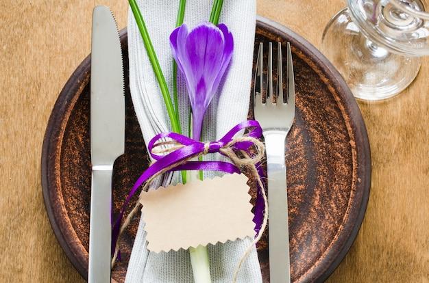 Ajuste festivo da tabela com flor e o cartão vazio.