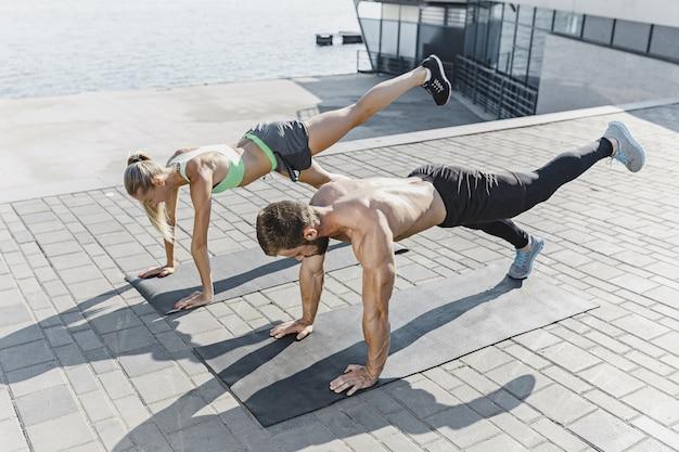 Ajuste fitness mulher e homem fazendo exercícios de fitness ao ar livre na cidade