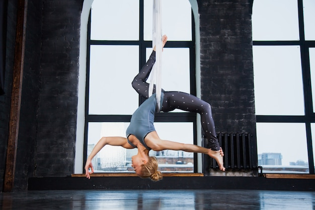 Ajuste flexível jovem mulher desportiva praticar ioga aérea na rede