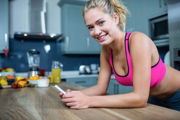 Ajuste menina enviando mensagens de texto na cozinha