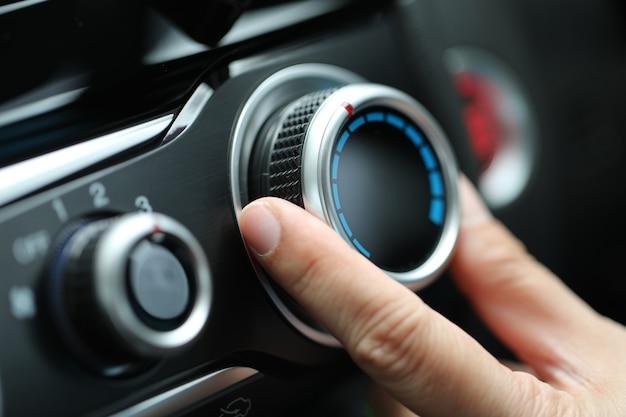 Ajuste o ar condicionado no painel do carro.